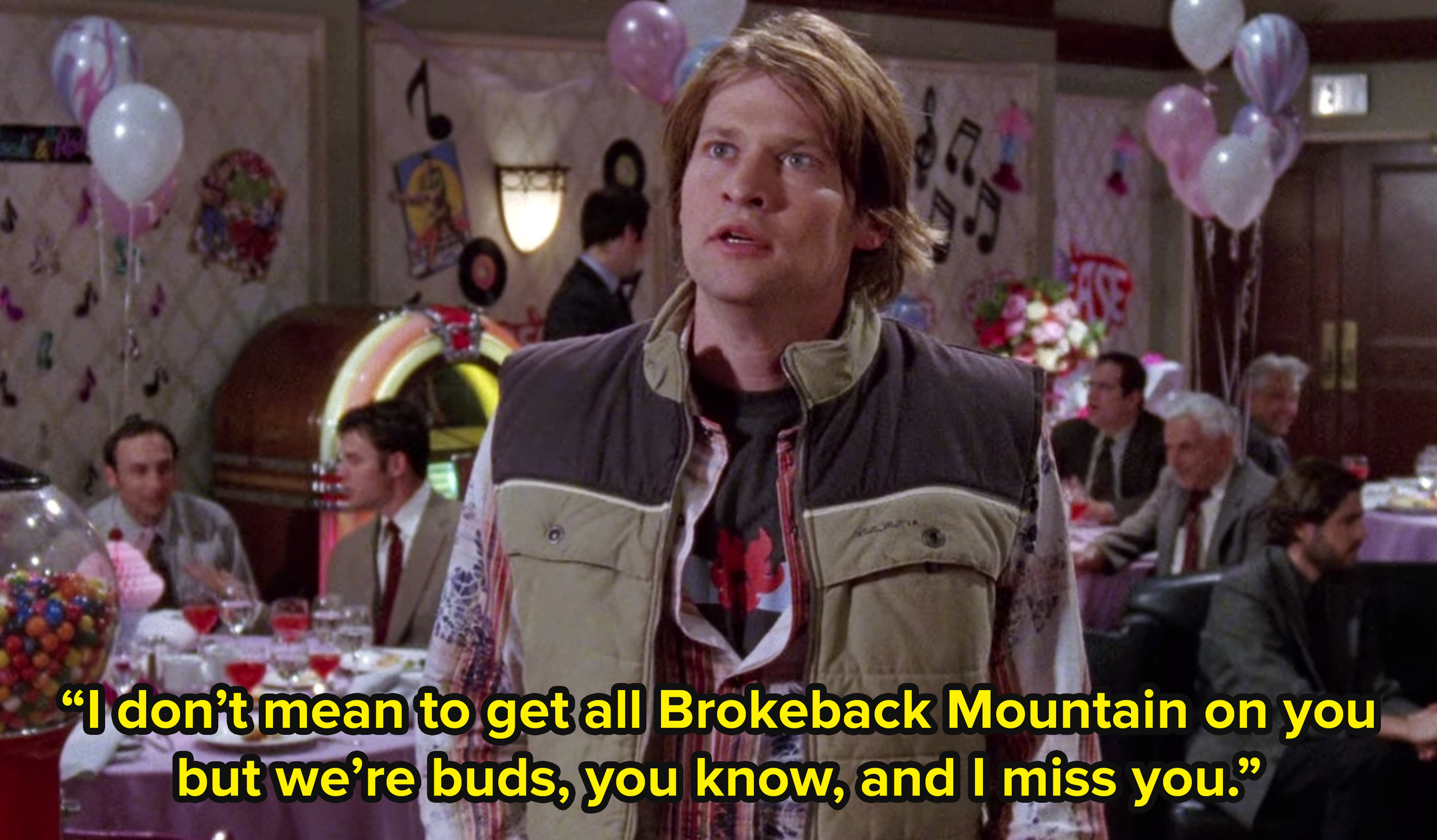 Zach from Gilmore Girls stands in the middle of a dinner function and addresses an unseen figure saying I don't mean to get all Brokeback Mountain on you but we're buds, you know, and I miss you