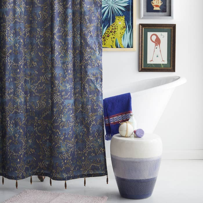a navy blue shower curtain with a boho design on it in lighter blue, tan, and gold with tiny fringes at the bottom