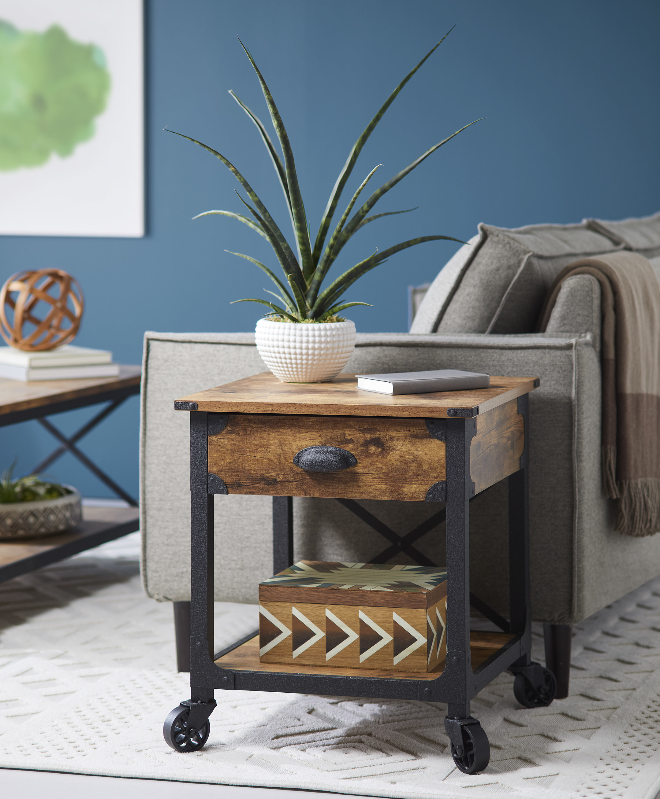 a wooden end table with black legs and wheels