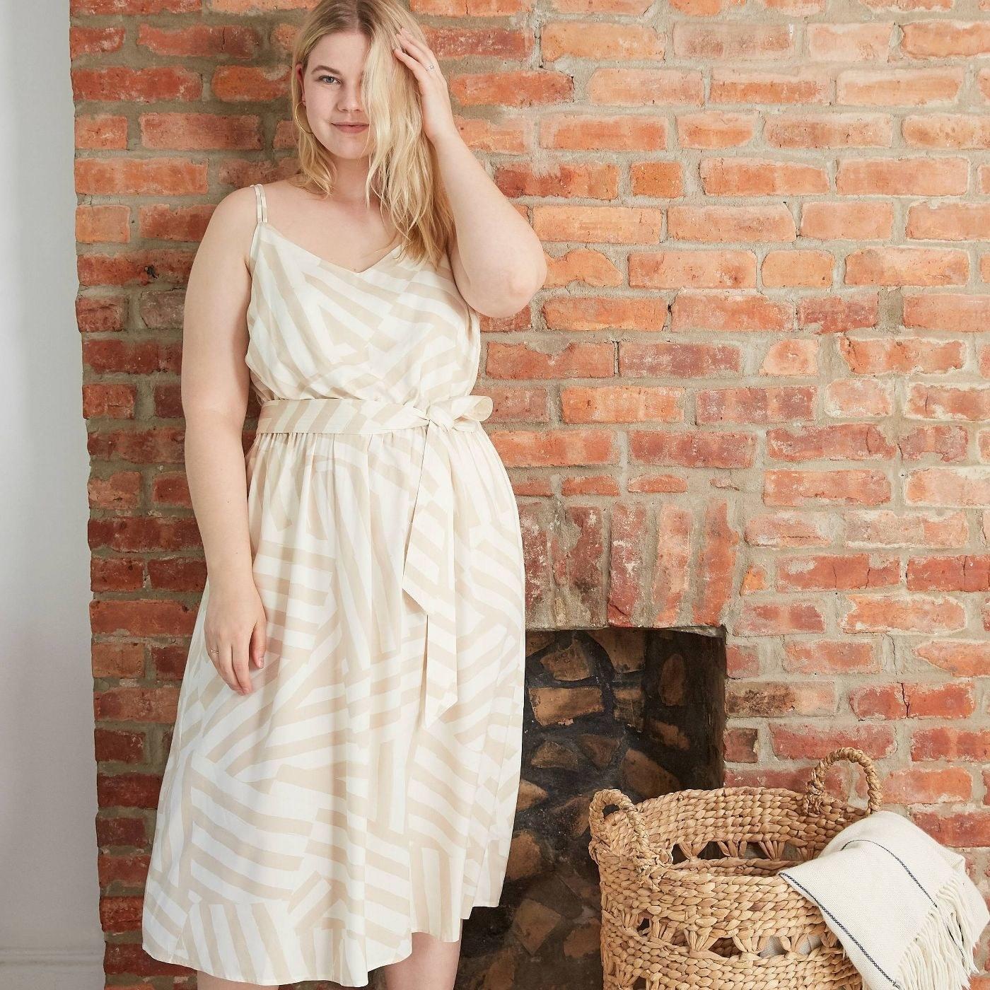 model wearing cream striped dress with tie waist