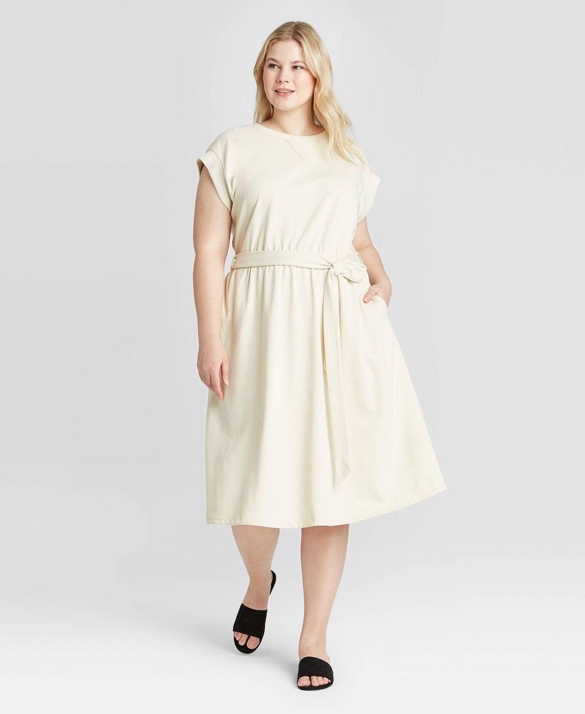 model wearing high-neck cream midi dress with tie waist