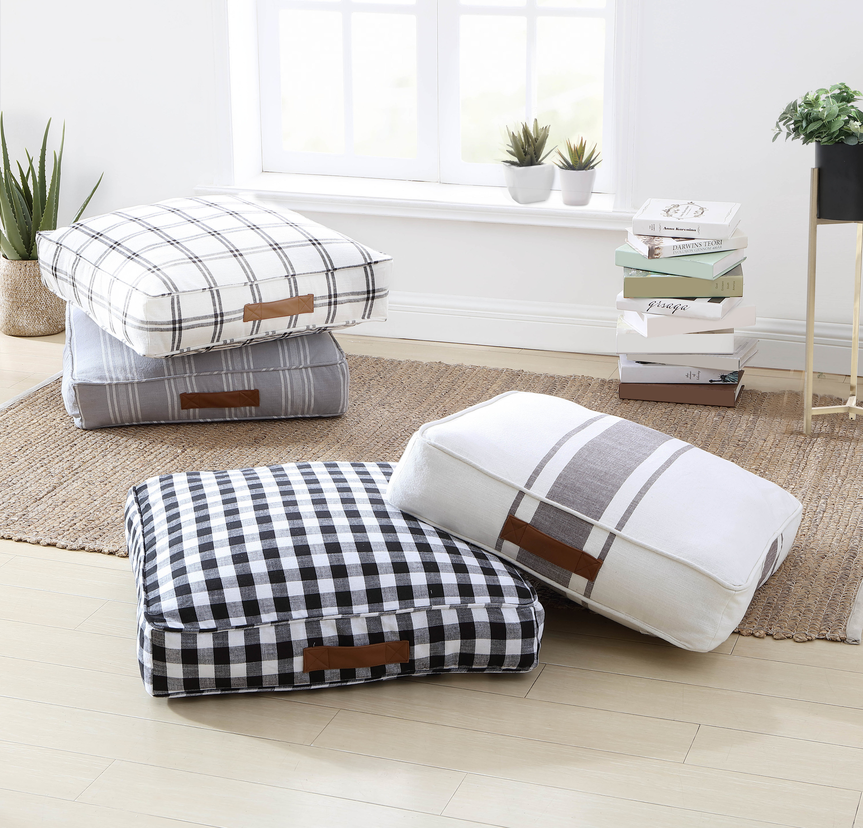 four square cushions with different patterns on the floor