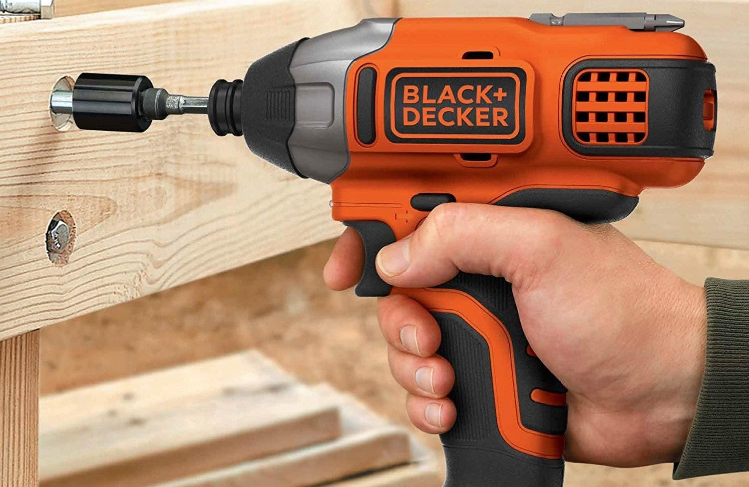 The Black + Decker cordless drill drilling into a piece of wood.