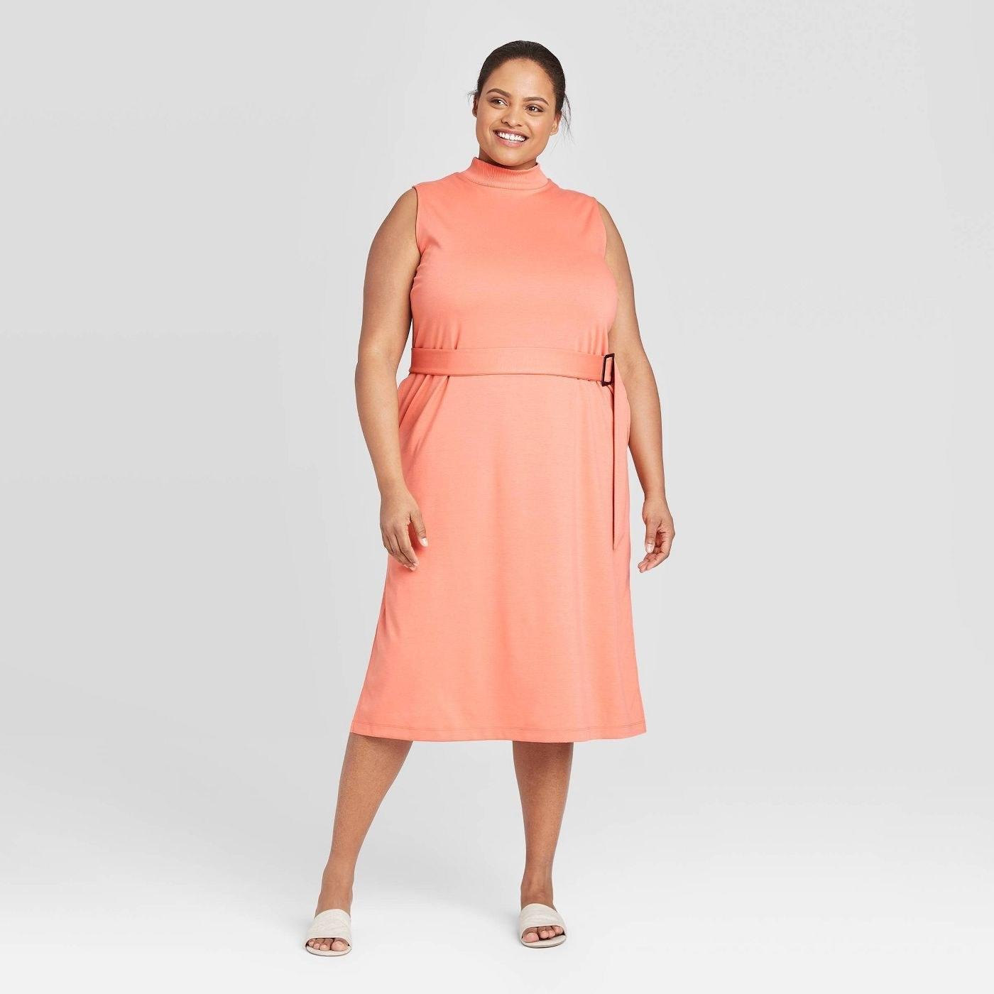 model wearing high-neck sleeveless orange midi dress