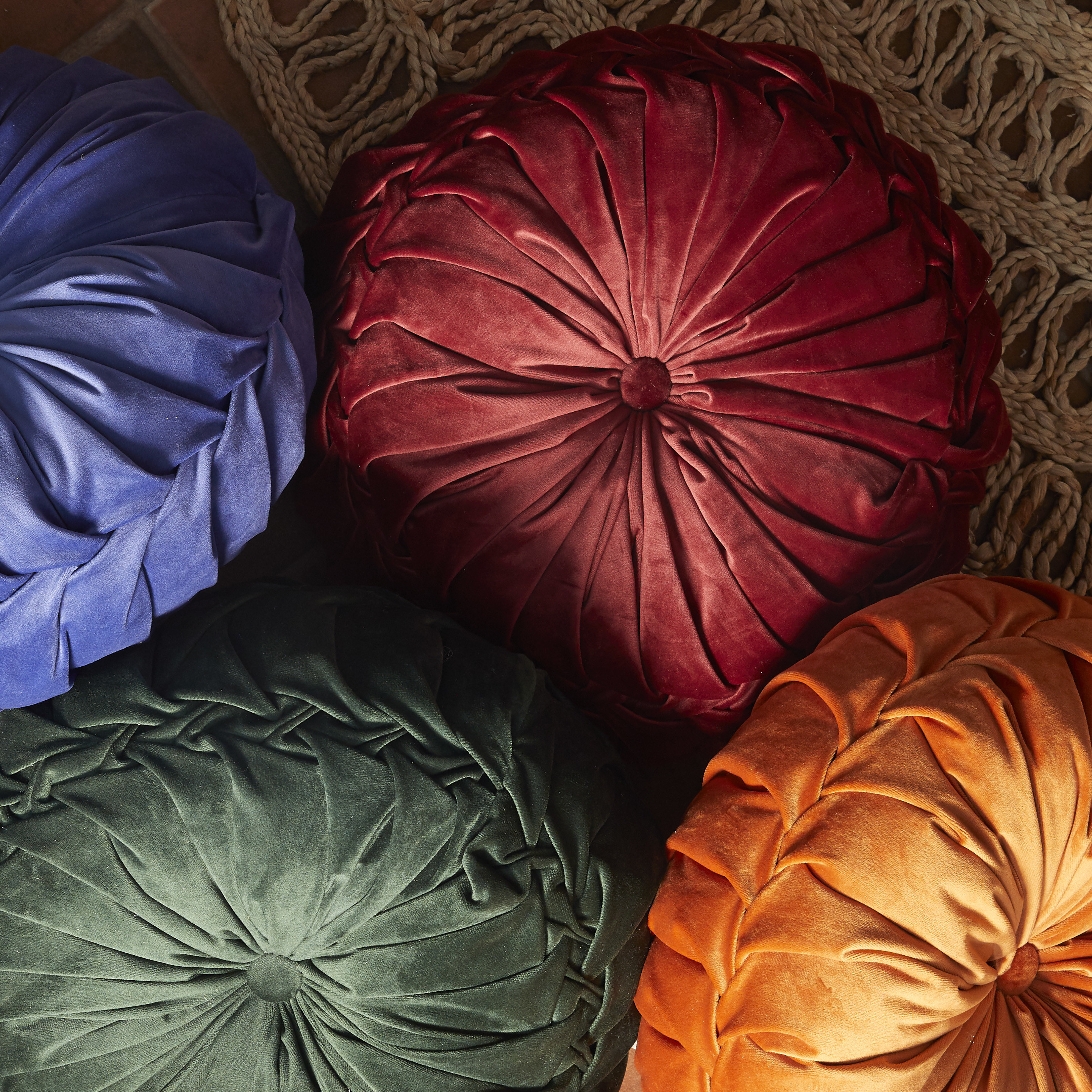 a pile of rounded velvet pillows in different colors