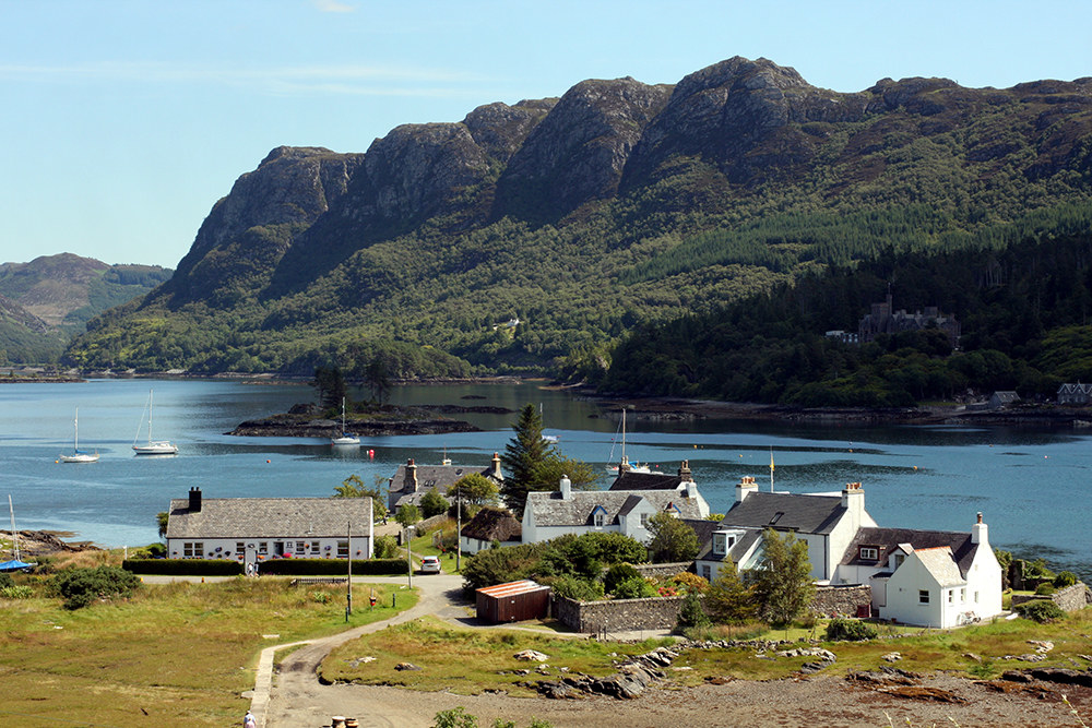 The small village of Plockton is in the forefront, with the Lock Carron behind as well as some tree covered mountains