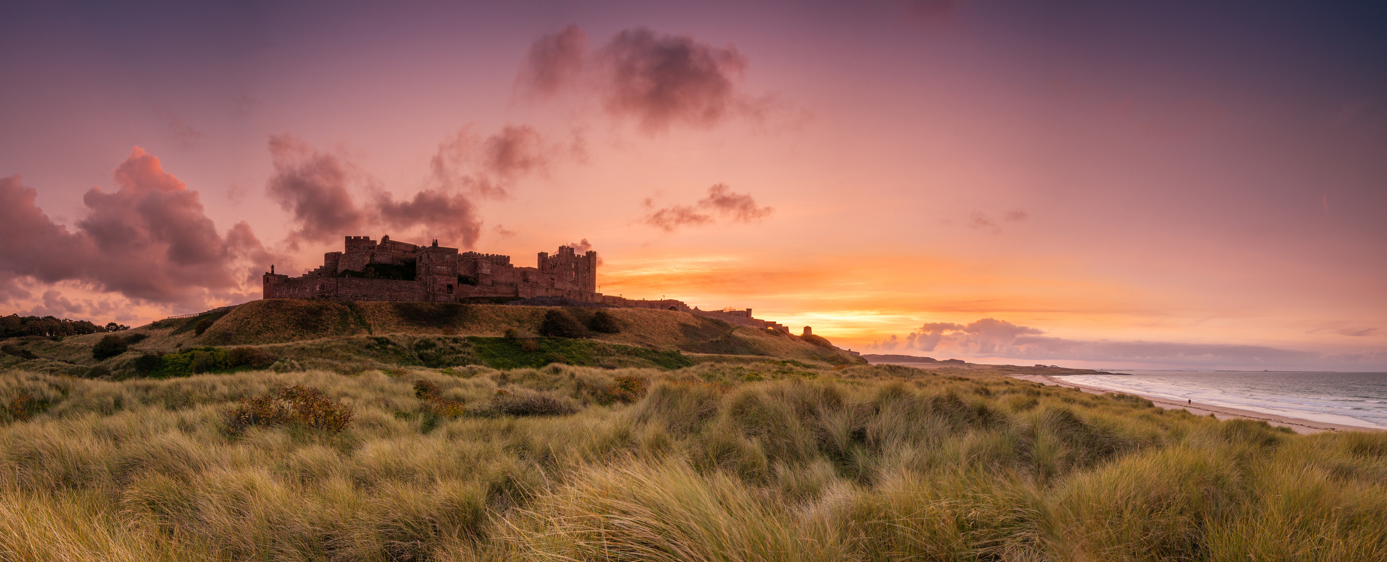 A pink and gold sunset view across Bamburgh castle and the beach in Northumberland