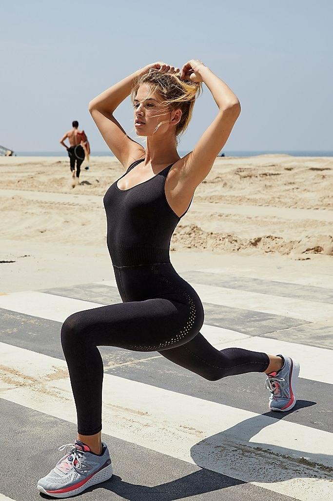 model wearing black U-neck stretch jumpsuit