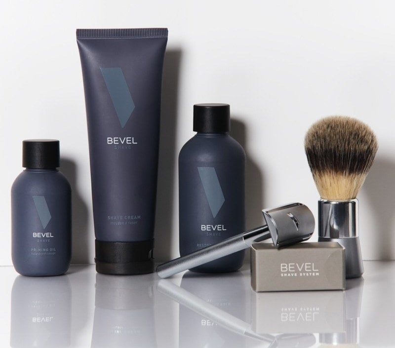 A silver razor and shaving brush with three dark blue bottles of shaving product