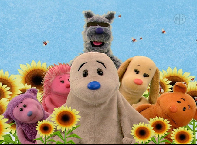 A group of animal puppets posing in a field of flowers