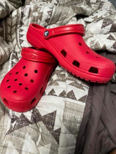 red pair of Crocs on a geometric print bedspread
