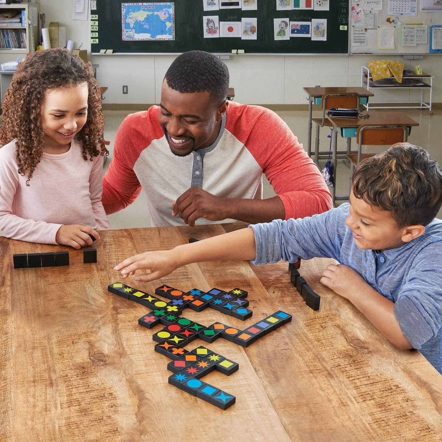 An adult model and two children playing board game with black bricks featuring colorful shapes