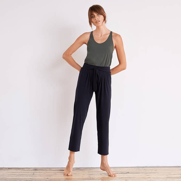 Model wearing the pants with pleats across the front and tie waist in navy