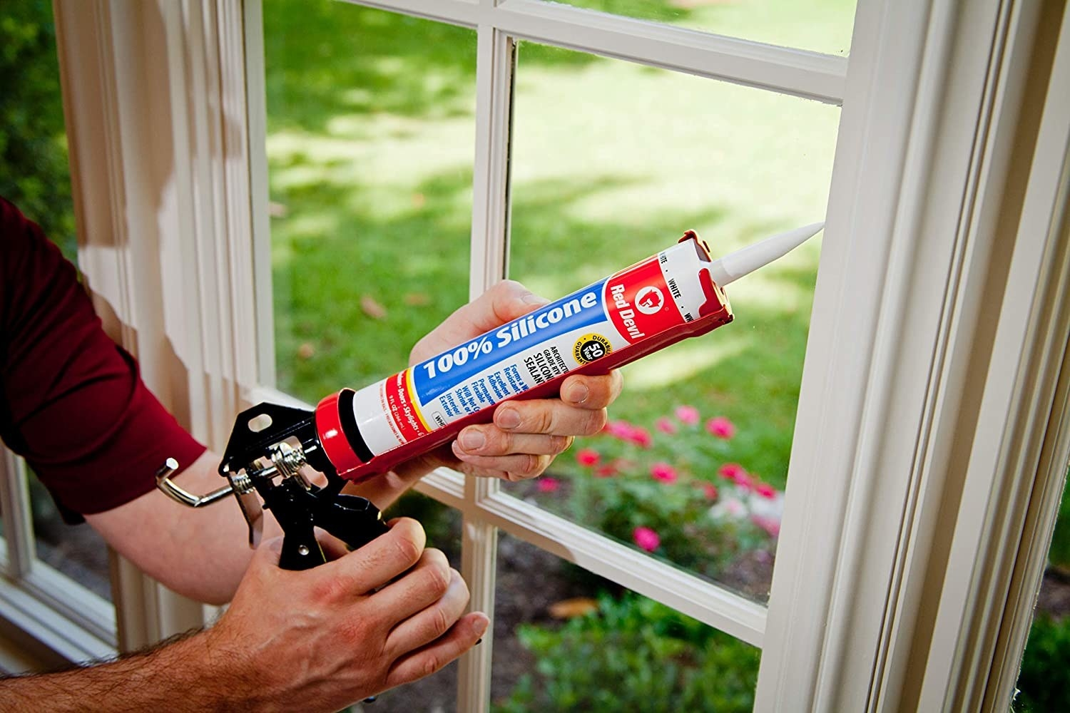 A person fixing a window frame with the caulking gun