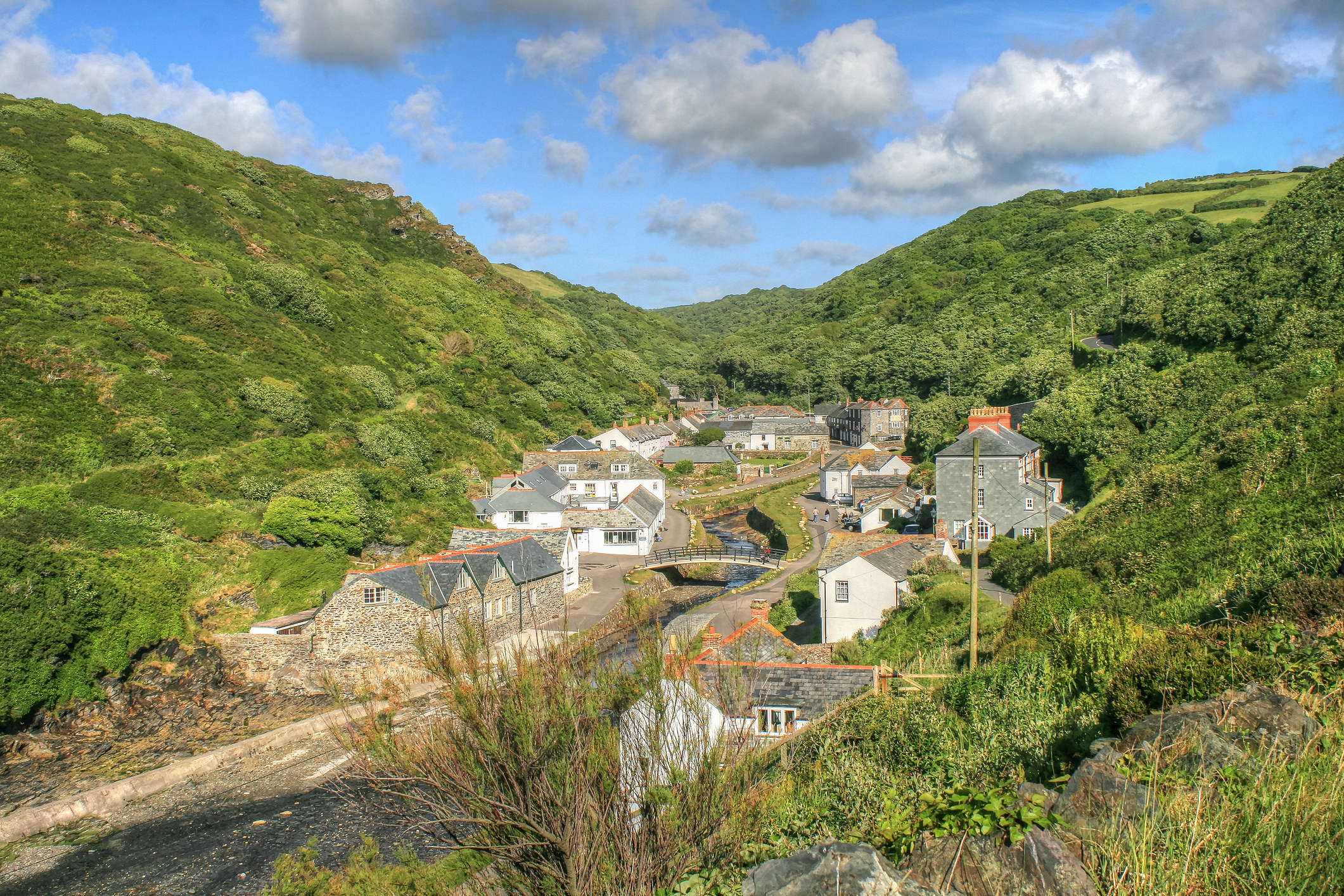 A view from above over the stone houses of the village as it sits in a valley with a river running through