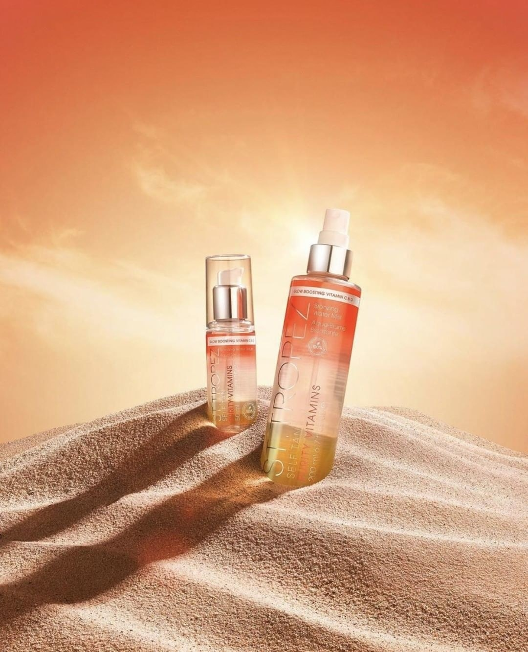 Two bottles of the Self Tan Purity Vitamins Bronzing Water Body Mist in a desert landscape