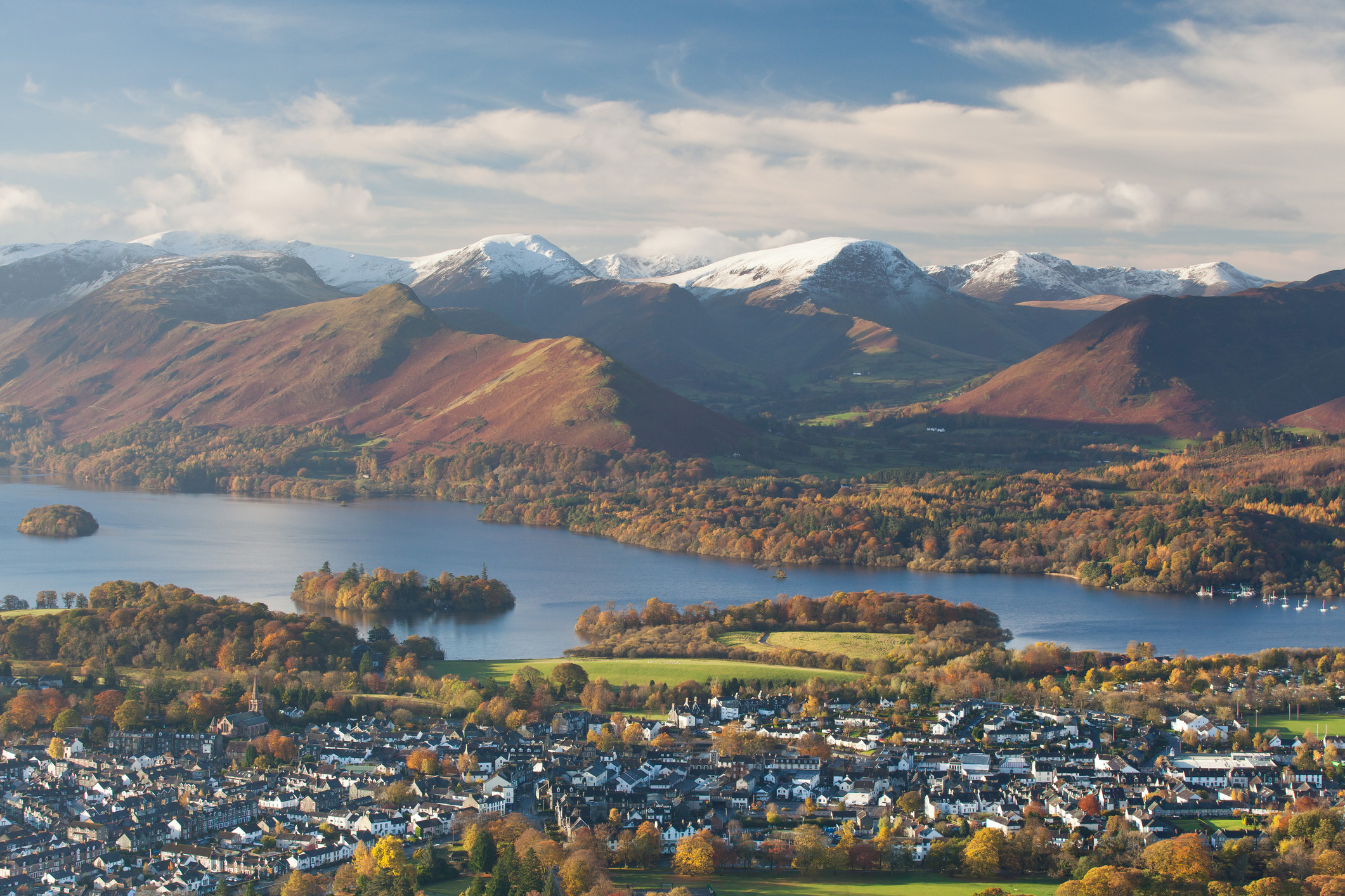 A view across the town of Keswick from above with the snow-capped mountains in the background