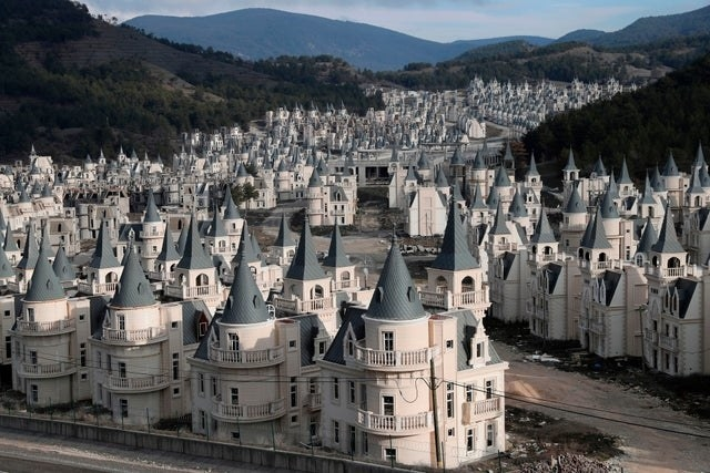 village of castles all identical with light grey bases and dark grey roof's in the base of a valley