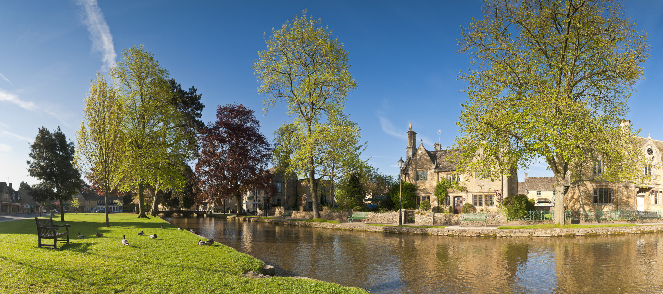 A view of the village's stone houses from over the River Windrush on a sunny and clear day