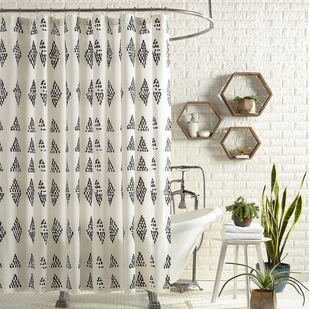 white shower curtain with irregular black dots forming a small diamond print