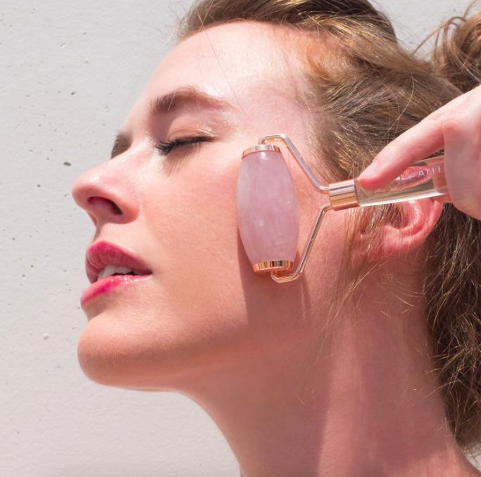 A model presses the facial roller into their face