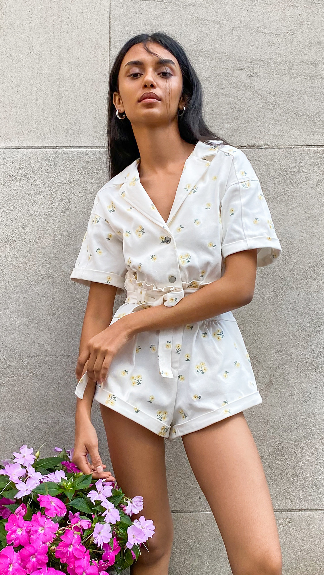 A model wearing the white romper with little yellow flower embroidery and cuffed shorts and short sleeves