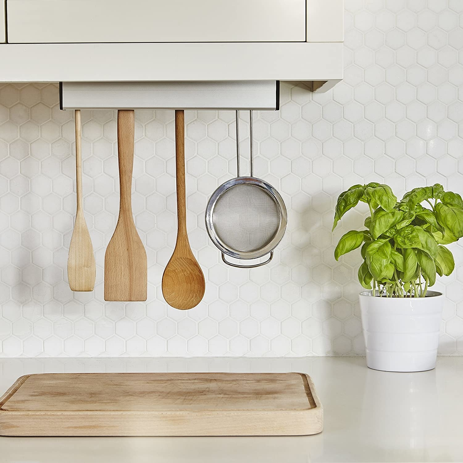 The utensil holder mounted under a cabinet and filled with wooden utensils and a stainless steel strainer