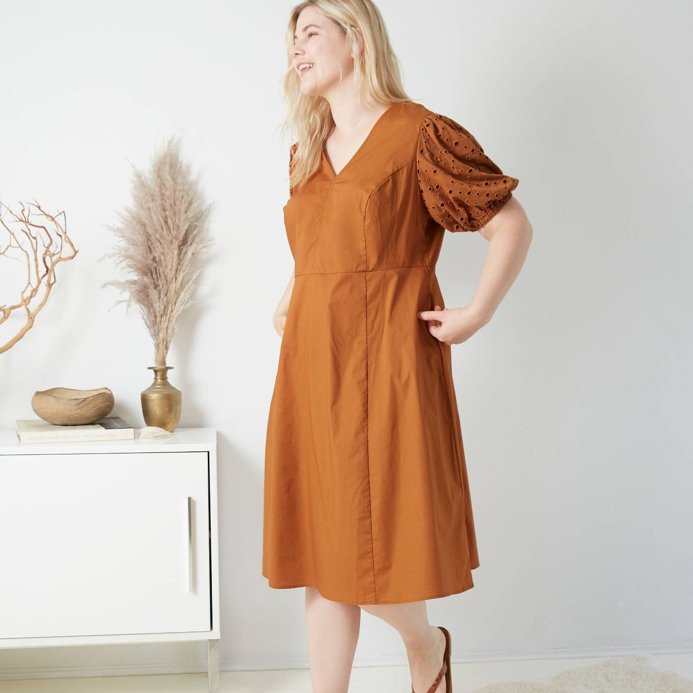 model wearing V-neck burnt orange dress with puffy sleeves