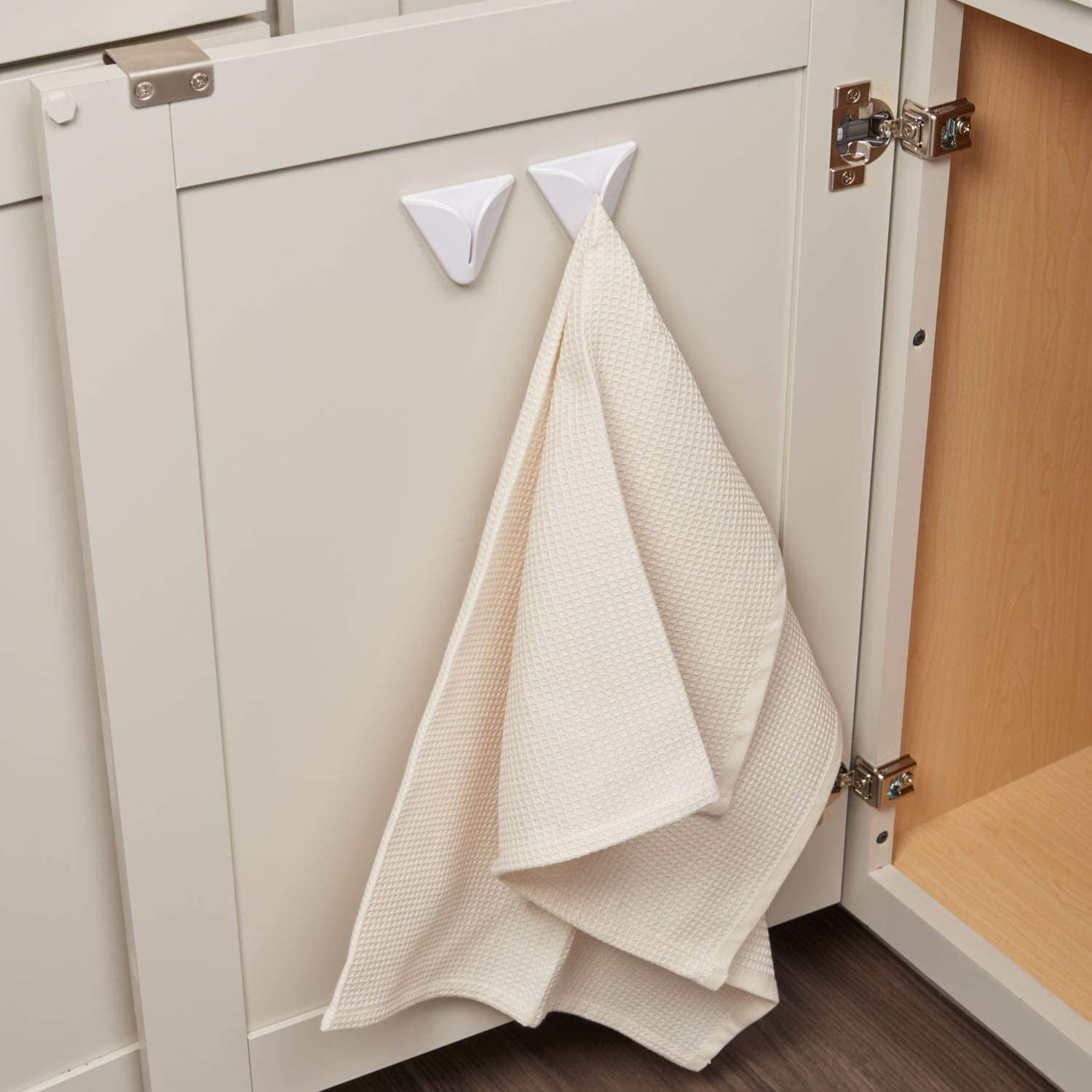 An open cabinet door with the two hooks installed on the inside and holding tea towels