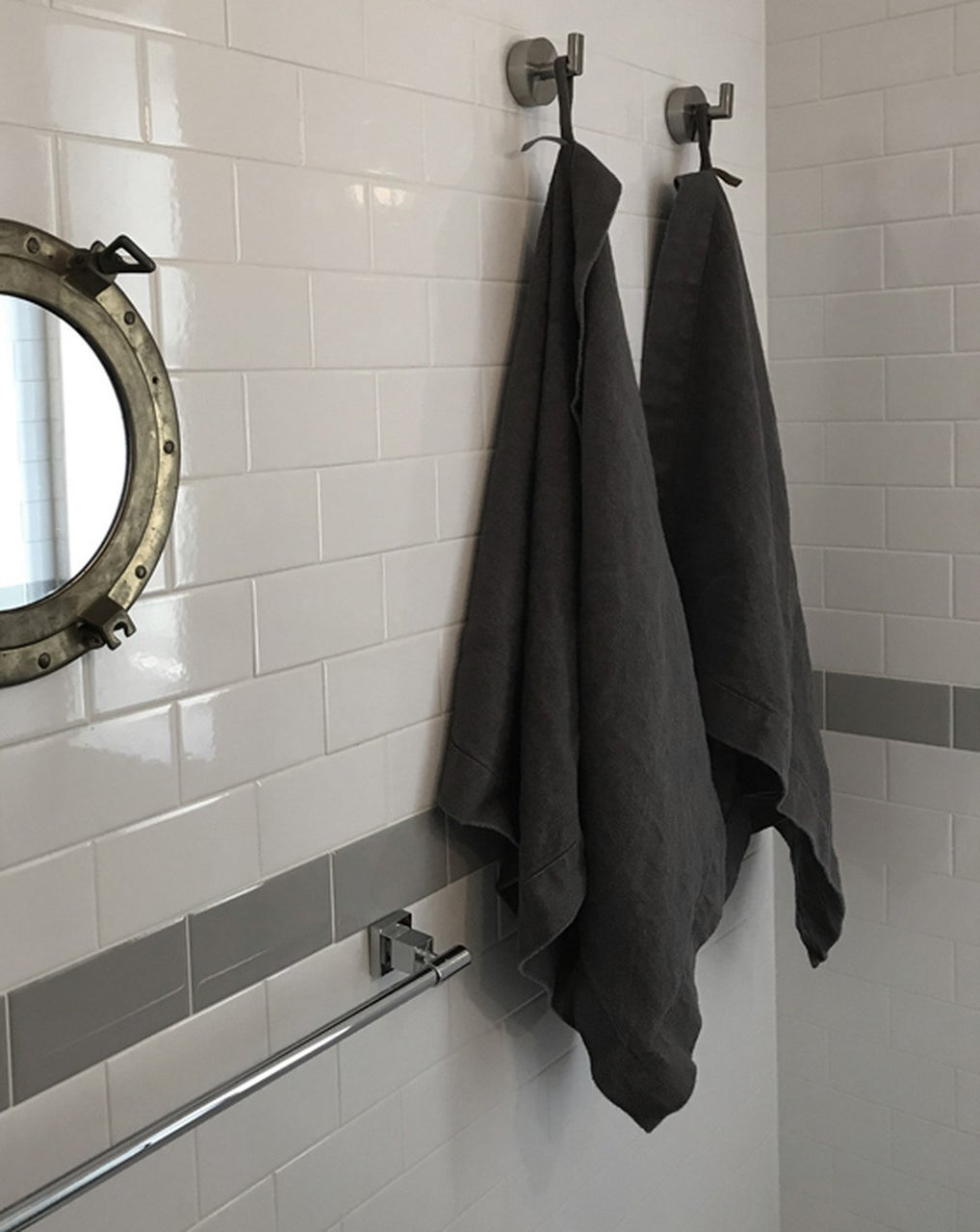 two dark grey linen bath sheets hangin on hooks