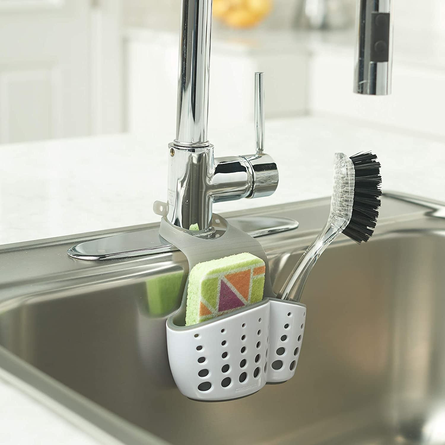 A whtie holder for a sponge and scrubber that hangs off the faucet of the sink