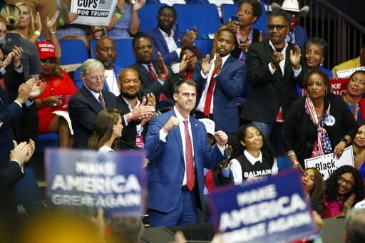 Gov. Kevin Stitt pumps his fists in the air while in the crowd at the president's rally in Tulsa.