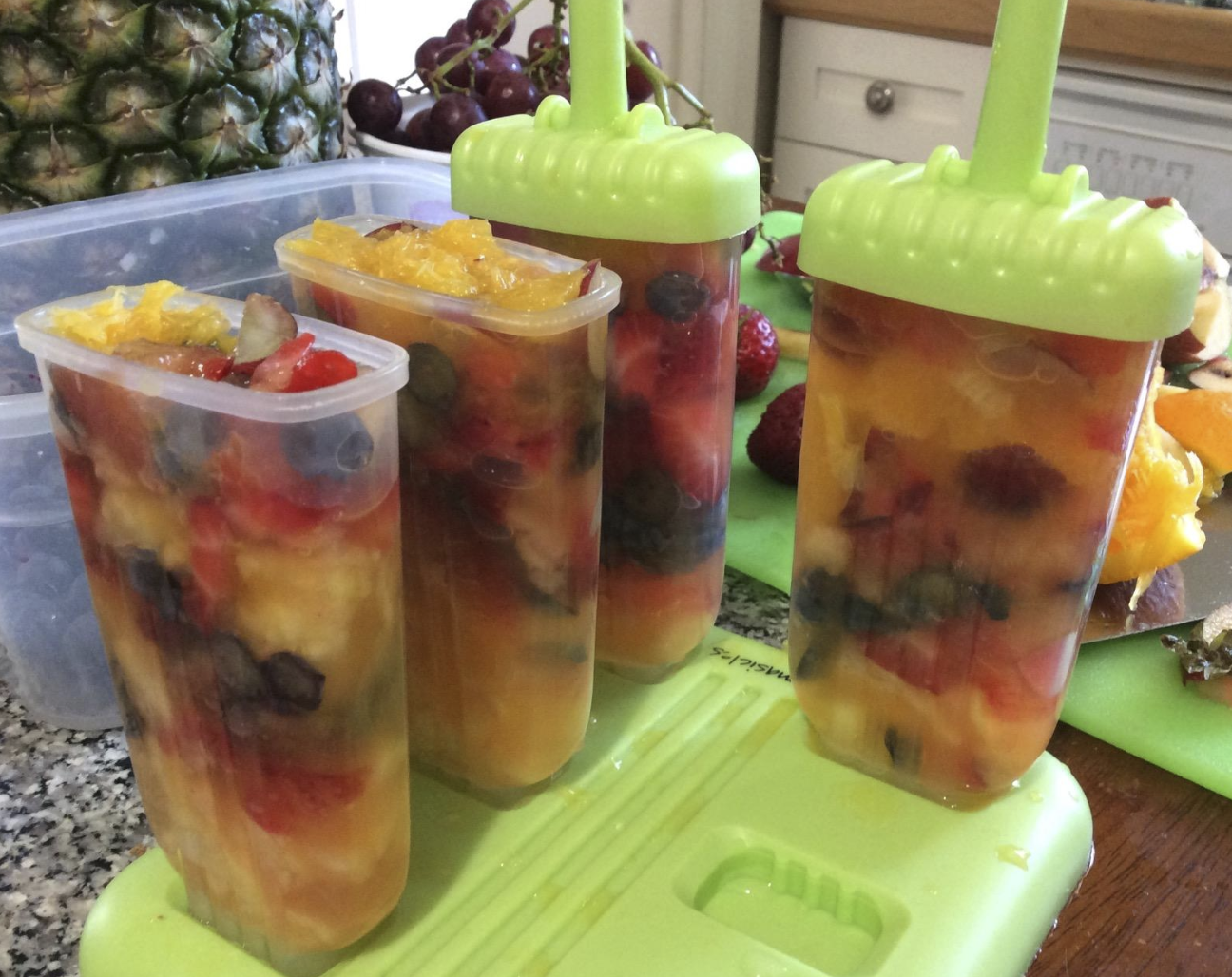 four popsicle containers filled with the fruit mix. Two have the tops on them that will serve as the sticks