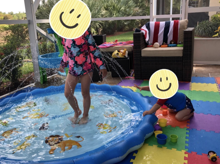 two kids playing in the circular play mat with water shooting out around the edges