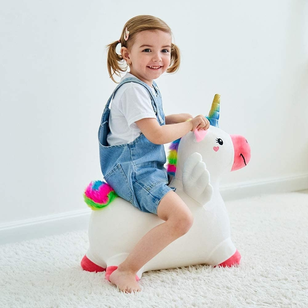 a toddler riding on the unicorn toy
