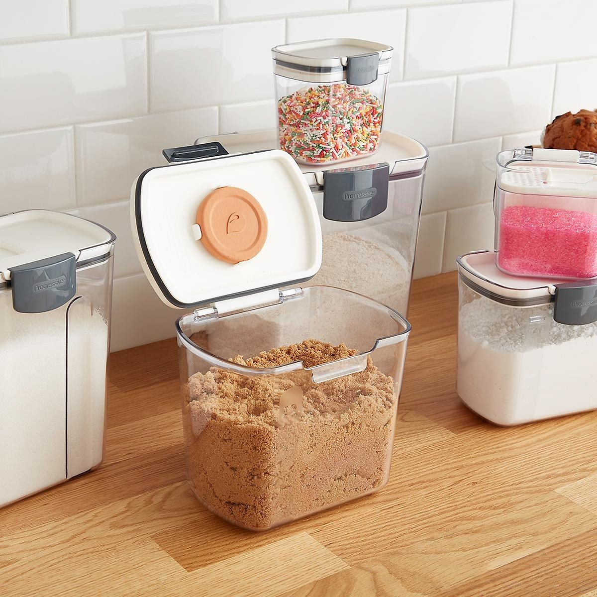 A clear storage container filled with brown sugar. The airtight lid is open to show the brown sugar keeper placed at the top.