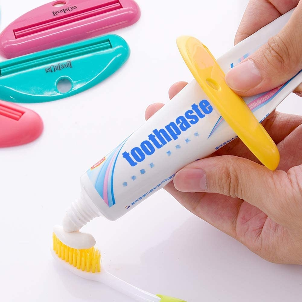 A person using the squeezer to put toothpaste on a brush