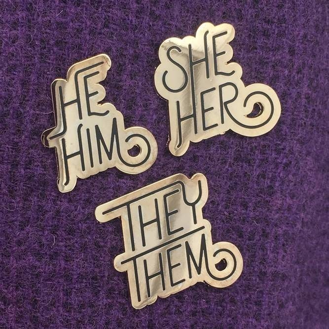A set of three pins. One says They Them, another She Her, and another says He Him.