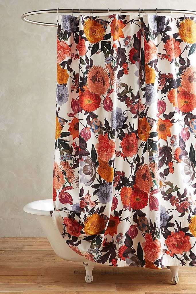 A white shower curtain that's covered in large poppies, tulips, and wildflowers of different shapes and colors. It is held up with traditional shower curtain rings.