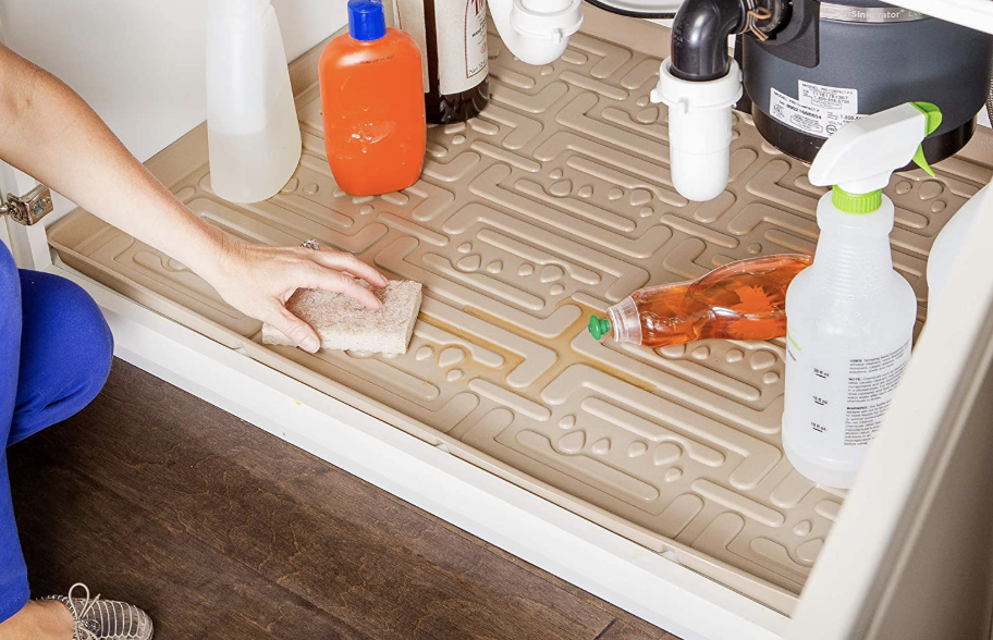 A model cleaning the grooves of the mat under a sink