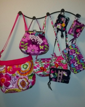 Reviewer's flower-printed purses and wristlets on a black wall hook