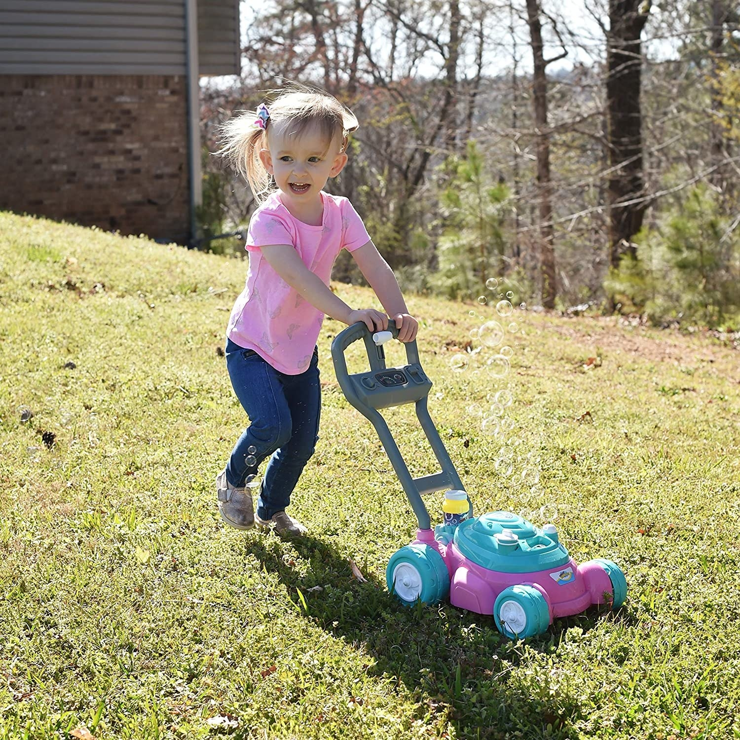 a child pushing the pink and teal blue lawn mower as bubbles rise from it
