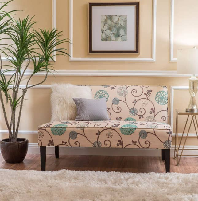 A pink green and blue floral-printed love seat in a living room