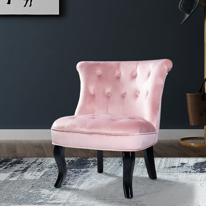 The light pink cushioned chair with a tufted back and seat, and black lacquered legs