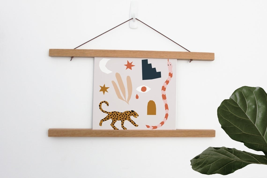 A print inside a hanger frame with abstract eyes, a moon, a leopard, a snake, and other mystical symbols and shapes.