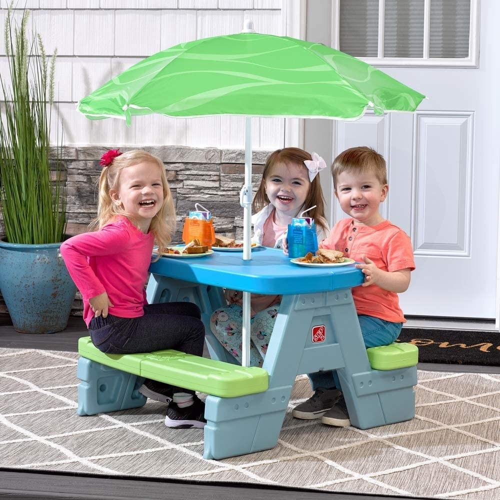 three kids eating lunch at a plastic picnic table under an umbrella