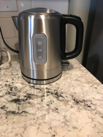 reviewer pic of stainless steel kettle with water indicator on side and black handle on marble kitchen countertop
