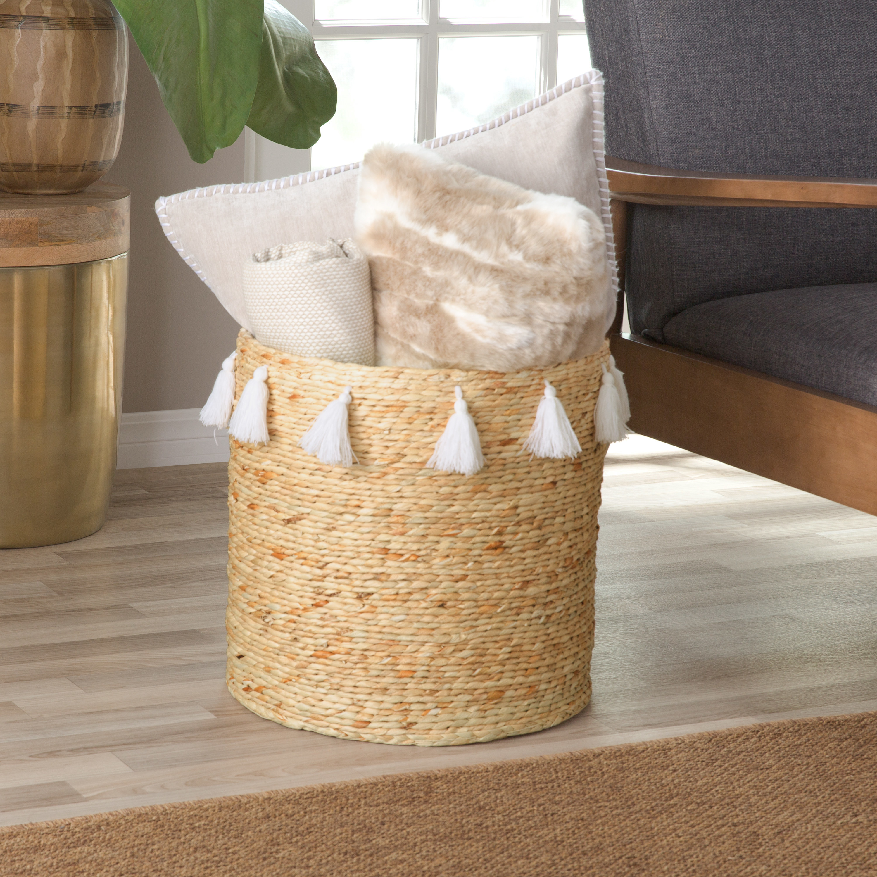 a light tan woven basket with white tassels hanging off the edge