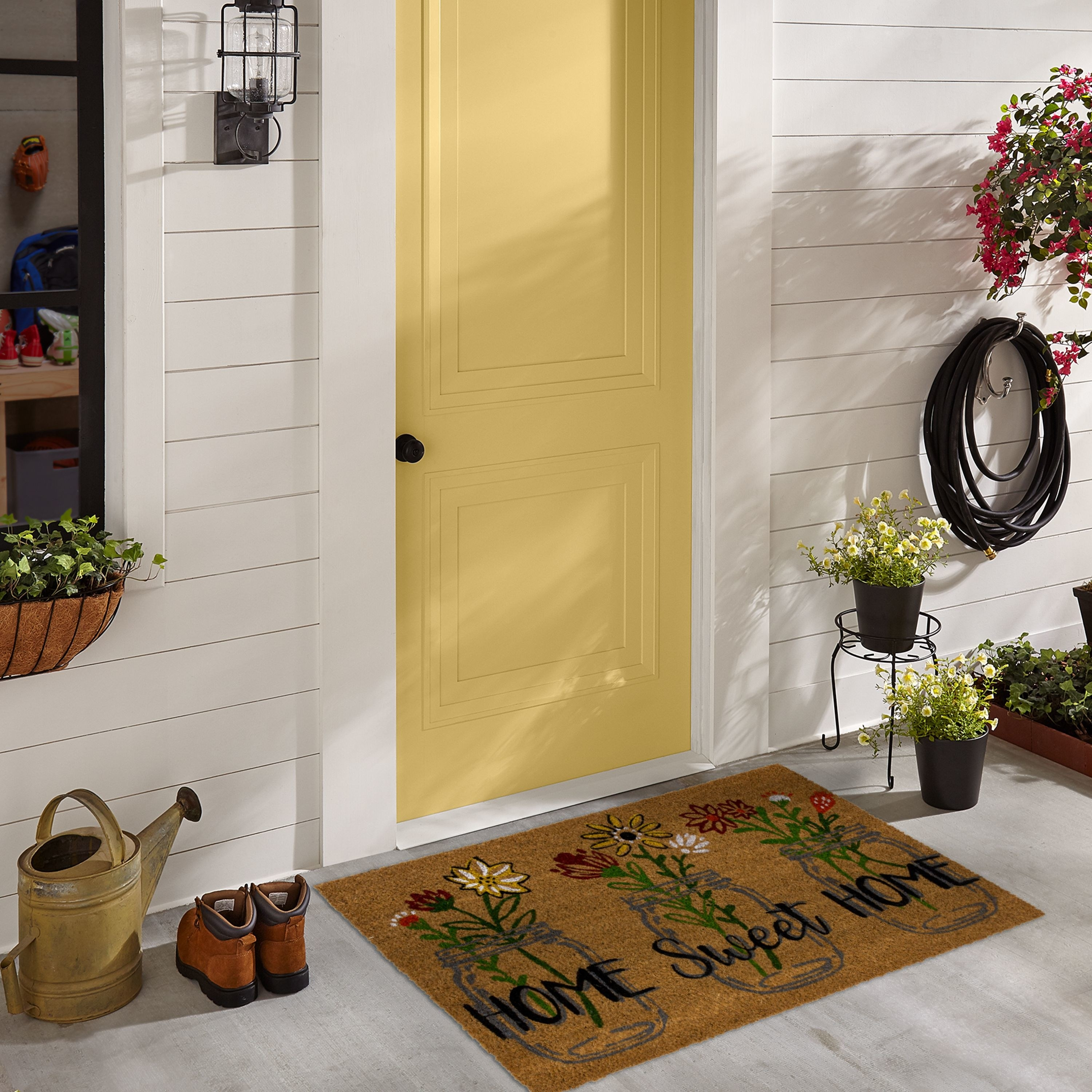 """a welcome mat with three mason jars filled with flowers on it and the words """"home sweet home"""""""
