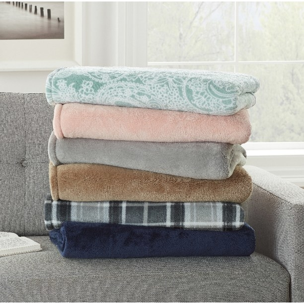 a stack of different colored plush blankets